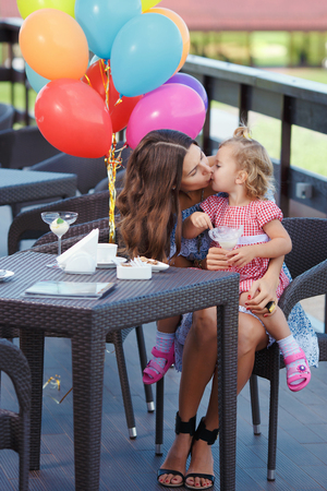 mother kissing daughter: Mother kissing daughter. Happy mom and daughter eating ice cream outdoors. Family sitting at a table in the outdoor cafe and eating ice cream. Stock Photo