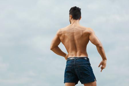 männer nackt: Muskulöser blanker Mann von hinten am Himmel Hintergrund Lizenzfreie Bilder