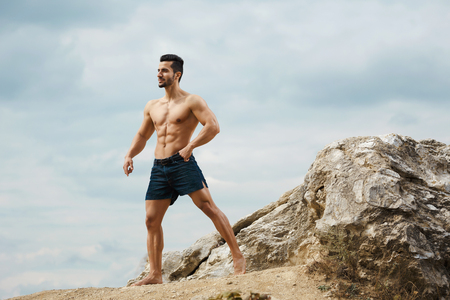 naked male body: Athletic and muscular man with naked torso stands on top of a mountain. Handsome young guy posing sporty appearance on the sky background, looking away Stock Photo