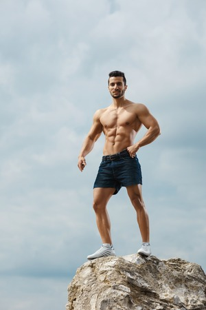 naked male body: Athletic and muscular man with naked torso stands on top of a mountain. Handsome young guy posing sporty appearance on the sky background