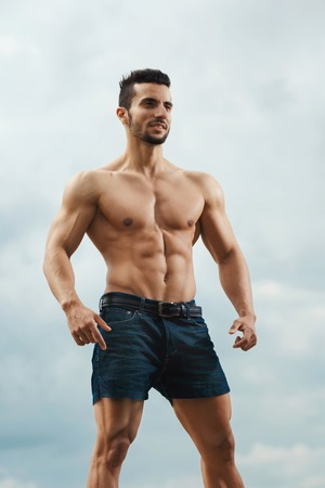 naked male body: Muscular male torso on a background sky. Athletic and muscular man with naked torso posing on the sky background, looking away