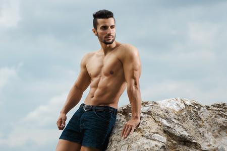 naked: Muskuläre männlichen Torso auf einem Hintergrund Himmel. Athletic und muskulösen Mann mit nackten Oberkörper befindet sich auf dem Gipfel eines Berges. Gut aussehender junger Mann posiert sportlichen Auftritt auf dem Himmel Hintergrund, Wegschauen Lizenzfreie Bilder