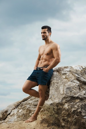 naked male body: stands on top of a mountain. Handsome young guy posing sporty appearance on the sky background, looking away