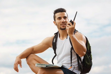 Hiker portrait. Explorer talking via radio station. Young man tourist with a backpack sitting on top of a mountain and holding map