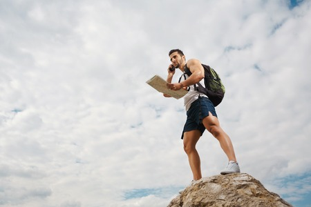 explorer man: Explorer talking via radio station. Young man tourist with a backpack standing on top of a mountain and holding map Stock Photo
