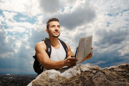 explorer man: Hiker portrait. Explorer talking via radio station. Young man tourist with a backpack sitting on top of a mountain and holding map