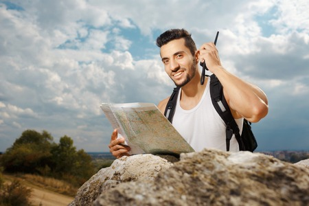 radio active: Hiker portrait. Explorer talking via radio station. Young man tourist with a backpack sitting on top of a mountain and holding map