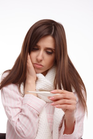 colds: Young sick woman in scarf and pajamas looking at thermometer. Sick girl with a thermometer on a white background, isolate, flu, colds