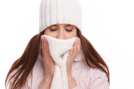 cold background: Young woman sick and closed with a scarf on white background. Sneezing into Tissue.