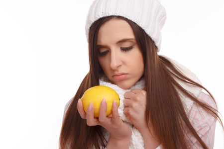 bad girl: Sick young woman in pajamas and scarf holding lemon on white background. Stock Photo