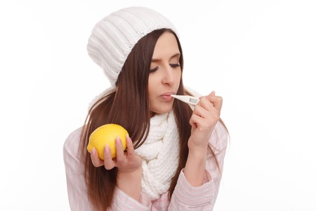 bad girl: A sick young woman measures the temperature and holding a lemon