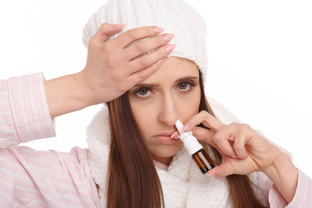 rheum: Sick young woman in pajamas scarf and hat use nasal spray. Woman applies nasal spray isolated. Sick Woman.Flu.Woman Caught Cold. Stock Photo