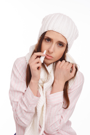 nasal drops: Sick young woman in pajamas scarf and hat use nasal spray. Woman applies nasal spray isolated. Sick Woman.Flu.Woman Caught Cold. Stock Photo