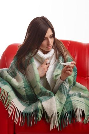 ragazza malata: Giovane donna malata in sciarpa e un pigiama guardando termometro. Ragazza ammalata con un termometro su uno sfondo bianco, isolare, influenza, raffreddore