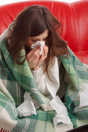 c vitamin: Sick young woman sitting on a red couch, and blowing his nose into a napkin. Woman sick blowing nose isolated. Sick Woman. Flu. Woman Caught Cold