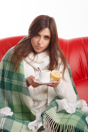 hot drinks: Sick young woman sitting on a red sofa and drinking tea with lemon. Young female caught cold, feeling bad, wrapped up in blanket, squeezing lemon to her tea.