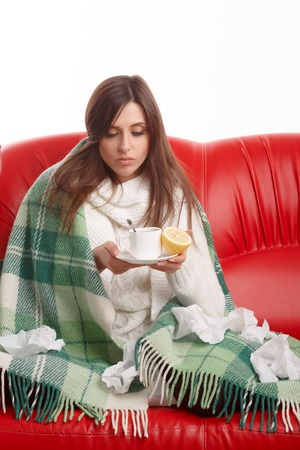 healthy girl: Sick young woman sitting on a red sofa and drinking tea with lemon. Young female caught cold, feeling bad, wrapped up in blanket, squeezing lemon to her tea.