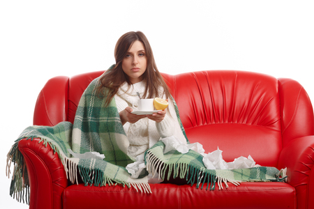feeling up: Sick young woman sitting on a red sofa and drinking tea with lemon. Young female caught cold, feeling bad, wrapped up in blanket, squeezing lemon to her tea.