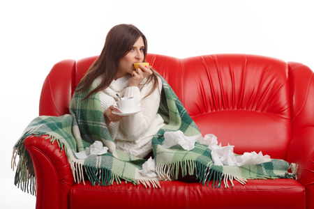 winter girl: Sick young woman sitting on a red sofa and drinking tea with lemon. Young female caught cold, feeling bad, wrapped up in blanket, squeezing lemon to her tea.