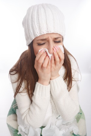 rheum: Sick young woman in pajamas scarf and hat coughing and blowing. Desperate and sick. Top view Stock Photo