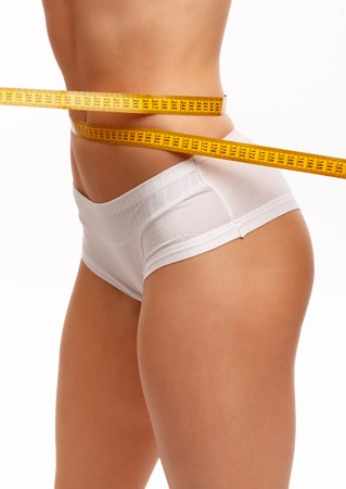 cintura perfecta: Perfect women body measuring waist. Isolation on white