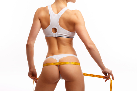 young woman measure her buttocks with a measuring tape
