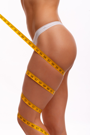 undressed woman: Woman measuring perfect shape of beautiful hips.Healthy lifestyles concept. Woman body part is being measured. Spa beauty part of body.Healthy lifestyle, diet and fitness. Perfect waist, butt and legs