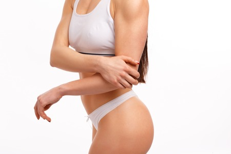 Sporty woman having pain in hers elbow on a white background, isolated