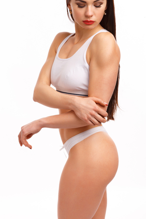 stretching condition: Sporty woman having pain in hers elbow on a white background, isolated
