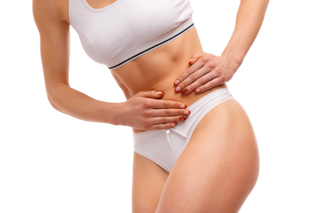 cramps: Stomach pain. Sport woman having abdominal pain, upset stomach or menstrual cramps. Pain in the abdomen, close-up