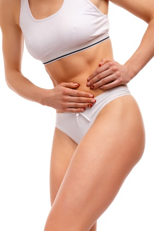 menstrual pain: Stomach pain. Sport woman having abdominal pain, upset stomach or menstrual cramps. Pain in the abdomen, close-up