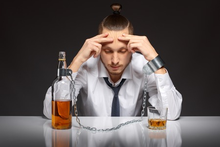 Young man businessman drinking whiskey with a feeling of despair. Addicted to alcohol, alcoholism concept, social problem Stock Photo