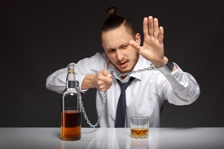 inebriated: Young man businessman trying to free from addiction to alcohol. Addicted to alcohol, alcoholism concept, social problem