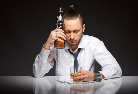 fetter: Young man businessman drinking whiskey with a feeling of despair. Addicted to alcohol, alcoholism concept, social problem Stock Photo