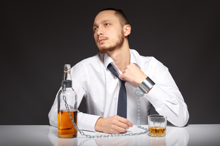 dipsomania: The young man feels suffocated by the habit to alcohol. Addicted to alcohol, alcoholism concept, social problem Stock Photo