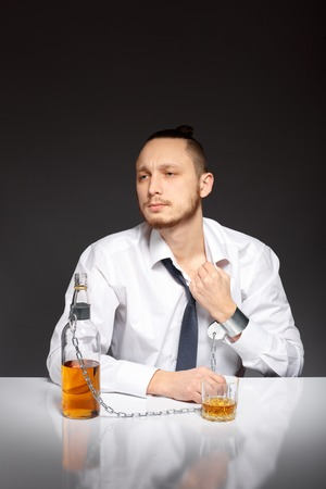 gyve: The young man feels suffocated by the habit to alcohol. Addicted to alcohol, alcoholism concept, social problem Stock Photo