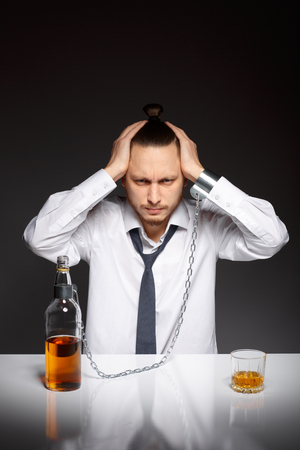 dipsomania: Young man holding his head in despair from the habit to alcohol. Addicted to alcohol, alcoholism concept, social problem