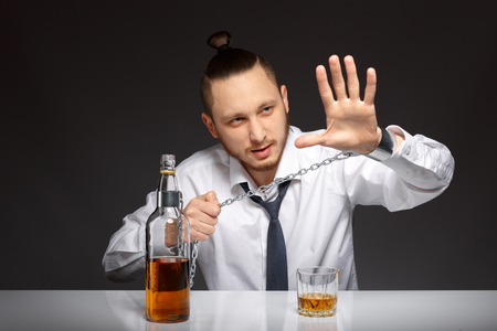 gyve: Emotional young businessman screaming STOP habit to alcohol. Addicted to alcohol, alcoholism concept, social problem Stock Photo
