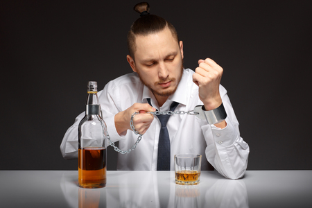 dipsomania: Young man businessman trying to free from addiction to alcohol. Addicted to alcohol, alcoholism concept, social problem