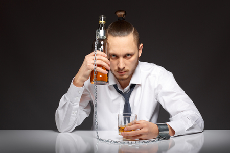 inebriated: Young man businessman drinking whiskey with a feeling of despair. Addicted to alcohol, alcoholism concept, social problem Stock Photo