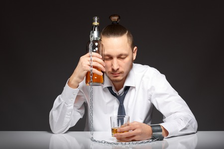 dipsomania: Young man businessman drinking whiskey with a feeling of despair. Addicted to alcohol, alcoholism concept, social problem Stock Photo