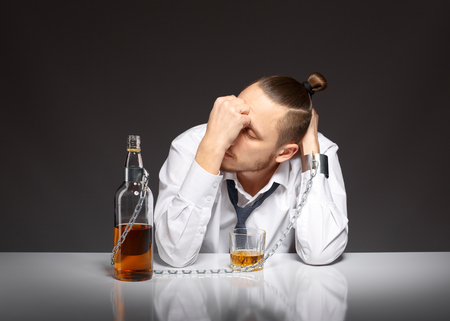 drunkenness: Young man businessman drinking whiskey with a feeling of despair. Addicted to alcohol, alcoholism concept, social problem Stock Photo