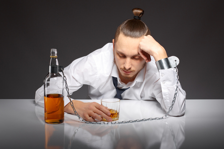 drinking problem: Young man businessman drinking whiskey with a feeling of despair. Addicted to alcohol, alcoholism concept, social problem Stock Photo