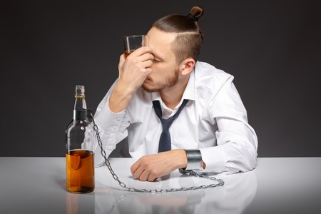 gyve: Young man businessman drinking whiskey with a feeling of despair. Addicted to alcohol, alcoholism concept, social problem Stock Photo