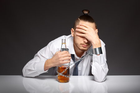 gyve: Man in despair of alcohol addiction holding his head. Addicted to alcohol, alcoholism concept, social problem