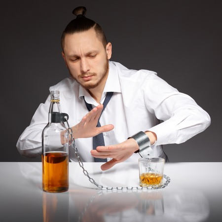 Young handsome man refuses to drink alcohol and alcohol dependence. Addicted to alcohol, alcoholism concept, social problem