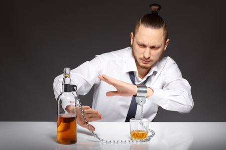 dipsomania: Young handsome man refuses to drink alcohol and alcohol dependence. Addicted to alcohol, alcoholism concept, social problem