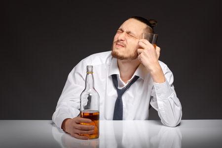 gyve: A young man in a white shirt sits at a table and suffers from a hangover Addicted to alcohol, alcoholism concept, social problem Stock Photo