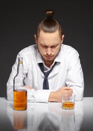 inebriated: A young man in a white shirt sits at a table and suffers from a hangover Addicted to alcohol, alcoholism concept, social problem Stock Photo