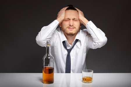 dipsomania: A young man in a white shirt sits at a table and suffers from a hangover Addicted to alcohol, alcoholism concept, social problem Stock Photo